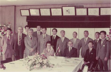 1977年:ハンガリー大臣来社岸野憲逸社長(後列中央左)、田中吾郎専務(後列中央右)(役職は来社当時のもの)